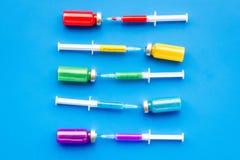 Medicinsk injektion Spola ren och buteljera med boten på bästa sikt för blå bakgrund Arkivbilder