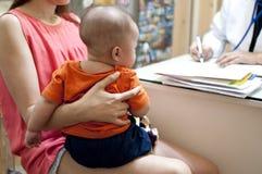 Medicinsk konsultation av en behandla som ett barnpojke arkivfoton