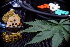 Medicinsk marijuanaproduktbakgrund med bladet, splittrar, slår ut royaltyfri foto