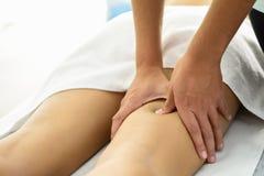 Medicinsk massage på benet i en sjukgymnastikmitt royaltyfri foto