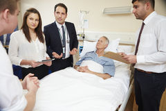 Medicinsk personal på rundor som står vid manlig patients säng royaltyfri bild