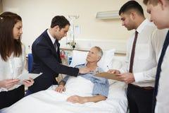Medicinsk personal på rundor som står vid manlig patients säng royaltyfria foton