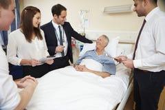 Medicinsk personal på rundor som står vid manlig patients säng arkivbilder