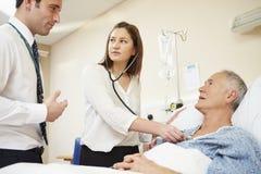 Medicinsk personal på rundor som undersöker den höga manliga patienten royaltyfria foton