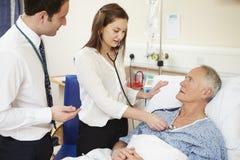 Medicinsk personal på rundor som undersöker den höga manliga patienten fotografering för bildbyråer