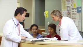 Medicinsk personal som arbetar på den upptagna sjuksköterskastationen arkivfilmer