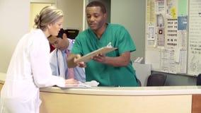 Medicinsk personal som arbetar på den upptagna sjuksköterskastationen stock video