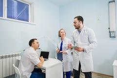 Medicinsk personal som diskuterar över medicinska rapporter genom att använda bärbar dator- och minnestavlaPC Sjukvårdprofessione arkivfoto