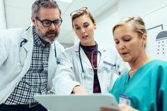 Medicinsk personal som diskuterar över medicinska rapporter i sjukhus arkivfoton