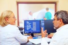 Medicinsk personal som diskuterar mriresultat under tillvägagångssätt Arkivfoto