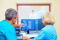 Medicinsk personal som diskuterar mriresultat under tillvägagångssätt Fotografering för Bildbyråer