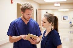 Medicinsk personal som ser den Digital minnestavlan i sjukhuskorridor royaltyfri fotografi