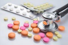 Medicinsk stetoskop och hög av piller arkivbilder