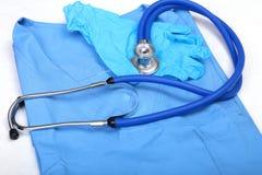 Medicinsk stetoskop och handskar som ligger på blått enhetligt doktorsslut upp Lagret av medicinska instrument och instrument Royaltyfria Foton
