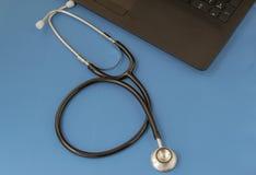 Medicinsk stetoskop och tangentbord på blå bakgrund Sjukv?rd royaltyfri fotografi