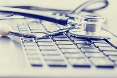 Medicinsk stetoskop på datortangentbordet