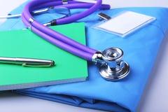 Medicinsk stetoskop som ligger på en blå närbild för form och för notepad för doktors` s utrymmet för arbete för terapeut` s arkivbilder