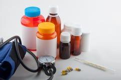 Medicinsk termometer, tonometer, preventivpillerar och flaskor Arkivfoton