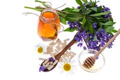 Medicinska örter, honung, naturliga kapslar och preventivpillerar i medicin royaltyfria foton