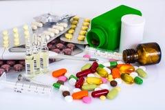 Medicinska ampules, flaskor, preventivpillerar och injektionssprutor, på vit Royaltyfria Bilder
