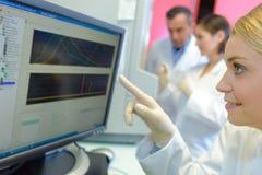 Medicinska forskare som använder digitalt maskineri på laboratoriumet arkivfoto
