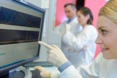 Medicinska forskare som använder digitalt maskineri på laboratoriumet royaltyfri foto