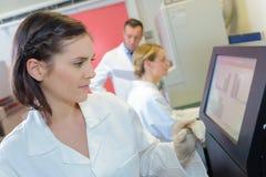 Medicinska forskare som använder digitalt maskineri på laboratoriumet royaltyfria foton