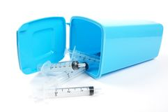 Medicinska injektionssprutor som ut faller ett blått fack royaltyfri foto