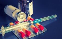 Medicinska objekt på mörk bakgrund - spola ren, den glass små medicinflaskor och packen av färgrik röstningcopyspace Arkivfoton