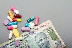 Medicinska preventivpillerar i olika färger och pengar Fotografering för Bildbyråer