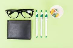 Medicinska preventivpillerar, kontorsblyertspennor och svart plånbok Royaltyfri Bild