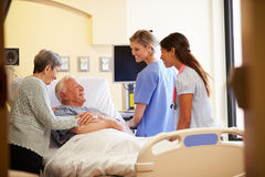 Medicinska Team Meeting With Senior Couple i sjukhusrum Royaltyfria Bilder