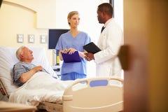 Medicinska Team Meeting With Senior Man i sjukhusrum Royaltyfria Foton
