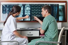 Medicinska tekniker som pekar på MRI-röntgenstrålen Fotografering för Bildbyråer