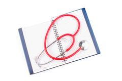 MEDICINSKT begrepp Stetoskop och öppen anteckningsbok på vita bakgrunder fotografering för bildbyråer