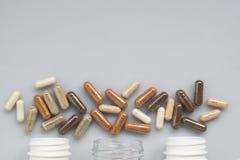Medicinskt kapselspill ut ur flaskor för en tre plast- på en ligh Arkivbild
