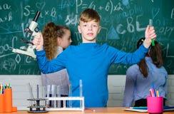 Medicinskt lag Små barn på skolakursen Små ungar som lär kemi i skolalabb Lyckliga barns dag royaltyfria foton