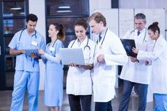 Medicinskt lag som använder bärbara datorn, den digitala minnestavlan och att diskutera röntgenstrålerapporten Fotografering för Bildbyråer