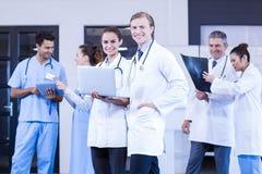 Medicinskt lag som använder bärbara datorn, den digitala minnestavlan och att diskutera röntgenstrålerapporten Arkivbild