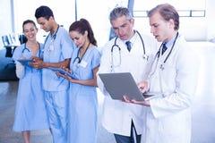Medicinskt lag som använder bärbara datorn och den digitala minnestavlan Royaltyfria Foton