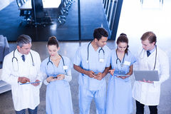 Medicinskt lag som använder mobil och digital minnestavlan den bärbar dator, Royaltyfri Bild