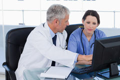 Medicinskt lag som fungerar samman med en dator Arkivfoton