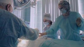 Medicinskt lag som utför en operation i sjukhus arkivfilmer