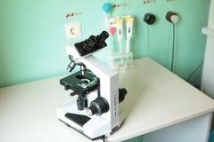 Medicinskt mikroskop och provrör på labbtabellen Arkivfoto