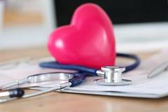 Medicinskt stetoskophuvud och röd leksakhjärta Arkivbilder