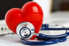 Medicinskt stetoskophuvud och röd leksakhjärta Royaltyfri Bild
