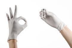 Medicinskt tema: doktors hand i en vit handske som rymmer en liten medicinflaska av klar flytande för injektionen som isoleras på Royaltyfri Foto