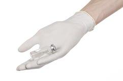 Medicinskt tema: doktors hand i en vit handske som rymmer en liten medicinflaska av klar flytande för injektionen som isoleras på Fotografering för Bildbyråer