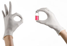 Medicinskt tema: doktors hand i en vit handske som rymmer en röd liten medicinflaska av flytande för injektionen som isoleras på  Arkivfoto