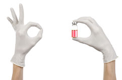 Medicinskt tema: doktors hand i en vit handske som rymmer en röd liten medicinflaska av flytande för injektionen som isoleras på  Royaltyfria Bilder